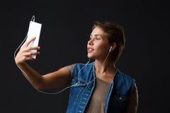 Den härliga flickan lyssnar till musik med hennes telefon på en svart bakgrund royaltyfri fotografi