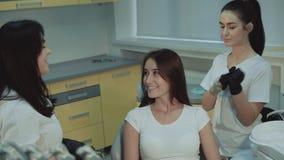 Den härliga flickan lyssnar till tandläkaren konsulterar, i stol och att le 4K stock video