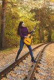 Den härliga flickan med den akustiska gitarren i höst parkerar arkivbild