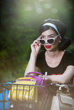 Den härliga flickan med den retro blicken som bär en svart dräkt som har gyckel parkerar in, med cykeln Utomhus- livsstilbegrepp  Arkivbild