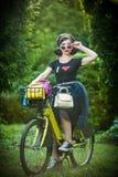 Den härliga flickan med den retro blicken som bär en svart dräkt som har gyckel parkerar in, med cykeln Utomhus- livsstilbegrepp  Royaltyfri Fotografi