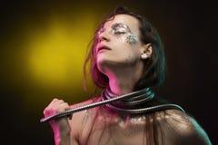 Den härliga flickan med det cretative sminket som göras av, blänker med revor på hennes framsida slår in hennes hals med en metal royaltyfria bilder