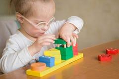 Den härliga flickan med Down Syndrome sorterar geometriska former Arkivbild
