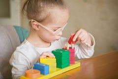Den härliga flickan med Down Syndrome sorterar geometriska former Royaltyfria Foton