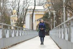 Den härliga flickan med en kamera går i parkera royaltyfri foto