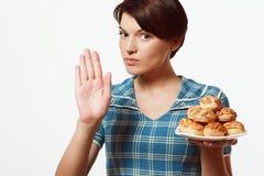 Den härliga flickan med en platta av bageriprodukter, bantar, kalorier Royaltyfria Foton
