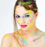 Den härliga flickan med färgrik målarfärg plaskar på framsida Royaltyfri Fotografi