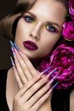 Den härliga flickan med färgrikt smink, blommor, retro frisyr och spikar länge Manikyrdesign Skönheten av framsidan royaltyfri foto