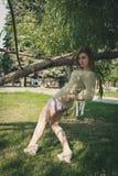 Den härliga flickan med flödande hår i korta kortslutningar som står i buktad, poserar nära ett träd på en bakgrund av gräsplan arkivbilder