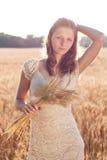 Den härliga flickan med gå i ax av vete i räcker på solnedgången royaltyfri fotografi