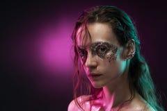 Den härliga flickan med idérik makeup som göras av, blänker med revor på hennes framsida som är upplyst med rosa färger, och blåt arkivfoton