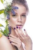 Den härliga flickan med konstsmink, blommor och design spikar manikyr Härlig le flicka arkivbild