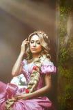 Den härliga flickan med långt hår som flätas i en flätad tråd, i korsett och storartade rosa färger, klär royaltyfri bild