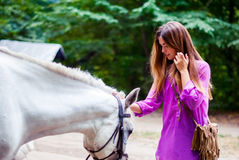 Den härliga flickan med långt hår stryker en vit häst Arkivfoto