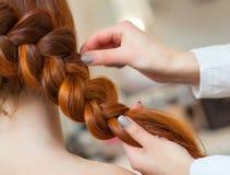 Den härliga flickan med långt rött hår, frisör väver en flätad tråd, i en skönhetsalong royaltyfri foto