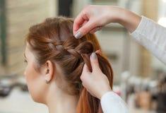 Den härliga flickan med långt rött hår, frisör väver en flätad tråd, i en skönhetsalong royaltyfri fotografi