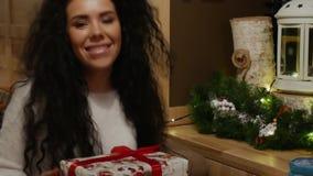 Den härliga flickan med lockigt hår ger en gåva för ` s för nytt år lager videofilmer