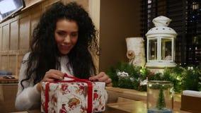 Den härliga flickan med lockigt hår ger en gåva för ` s för nytt år i kafé stock video