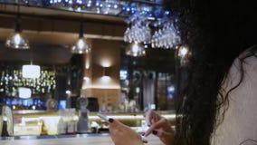 Den härliga flickan med lockigt hår i en restaurang är den rörande telefonen och leendet lager videofilmer