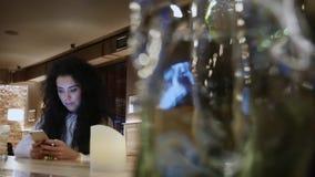 Den härliga flickan med lockigt hår i en restaurang arbetar på telefonen och leende stock video