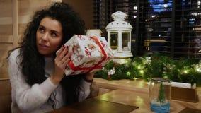 Den härliga flickan med lockigt hår mottog en gåva för nytt år i restaurangen lager videofilmer