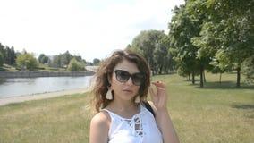Den härliga flickan med lockigt hår som ser kameran i en stad, parkerar och med en flod i bakgrunden lager videofilmer