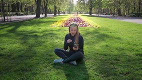 Den härliga flickan med minnestavladatoren sitter på gräs arkivfilmer