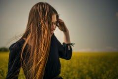 Den härliga flickan med rött hår går utomhus över fältet Arkivfoton
