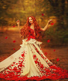 Den härliga flickan med rött hår i höst parkerar royaltyfria bilder