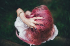 Den härliga flickan med rosa hår sitter på den kastade stegen i en miljö av ett grönt gräs Royaltyfria Foton