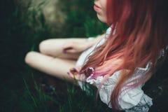Den härliga flickan med rosa hår sitter på den kastade stegen i en miljö av ett grönt gräs Royaltyfri Fotografi
