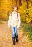 Den härliga flickan med ryggsäcken står i skog Royaltyfri Foto