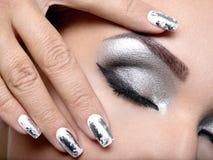 Den härliga flickan med silvermakeupen och spikar royaltyfria foton