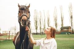 Den härliga flickan meddelar med en häst i parkera Royaltyfri Foto