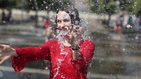 Den härliga flickan omfamnar grabben i springbrunnen stock video