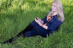 Den härliga flickan på ett gräs med telefonen Arkivbild