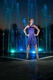 Den härliga flickan på utomhus- bevattnar springbrunnen i en natt fotografering för bildbyråer