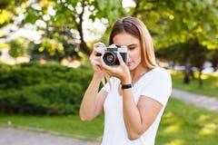 Den härliga flickan parkerar in att ta fotografier med hennes parallella kamera Royaltyfri Foto