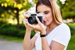 Den härliga flickan parkerar in att ta fotografier med hennes parallella kamera Arkivbild