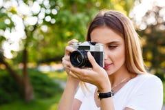 Den härliga flickan parkerar in att ta fotografier med hennes parallella kamera Royaltyfria Bilder