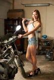 Den härliga flickan poserar med en skiftnyckel nära motorcykeln royaltyfri fotografi