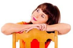 Den härliga flickan poserar och att sitta på en stol Royaltyfria Bilder