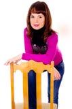 Den härliga flickan poserar och att sitta på en stol Arkivbilder