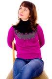 Den härliga flickan poserar och att sitta på en stol Arkivbild