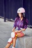 Den härliga flickan sätter på det skyddande kugghjulet för rollerblading royaltyfri fotografi