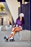 Den härliga flickan sätter på det skyddande kugghjulet för rollerblading arkivbild