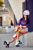 Den härliga flickan sätter på det skyddande kugghjulet för rollerblading royaltyfria foton