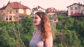Den härliga flickan, ser framåtriktat på bakgrund av gröna träd, hus, natur, blont hår går arkivfilmer