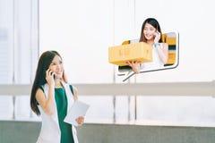 Den härliga flickan shoppar genom att använda smartphonen, online-köpmannen levererar packen Ecommercekommunikation, begrepp för  fotografering för bildbyråer