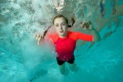 Den härliga flickan simmar undervattens- i en röd baddräkt på en blå bakgrund och ser mig Stående Närbild Landskaporientat Royaltyfri Foto